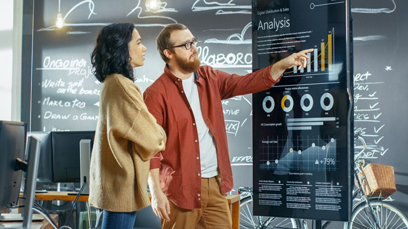 man and woman looking at analysis chart