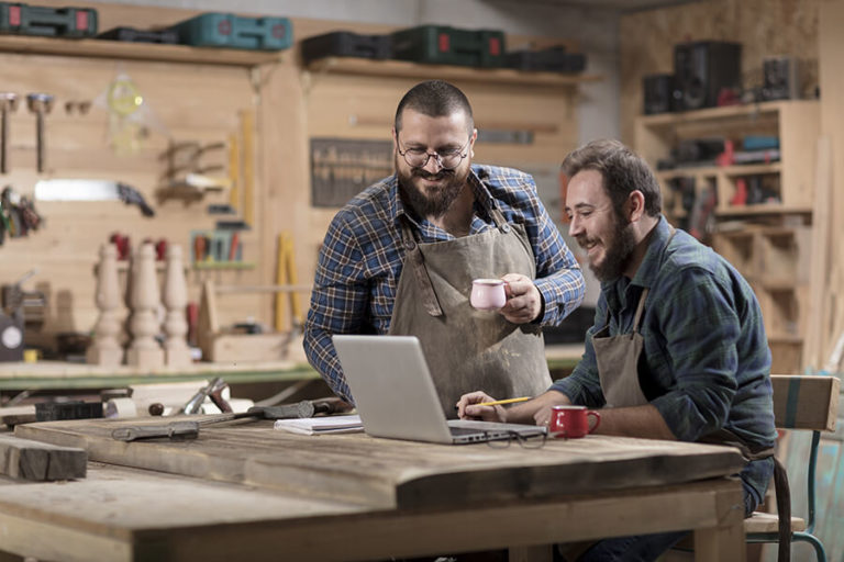 two happy small business men looking at laptop in workshop